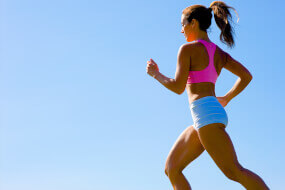 Woman in shorts and sports bra jogging against a blue sky