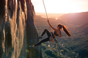 Athletic woman climbing a mountain on a rope