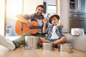 Father and his son playing the guitar and pots as drums