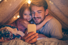 Father with his daughter in a tent looking at a phone screen