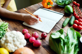 Woman writing in a notebook a meal plan with fresh vegetables on the table
