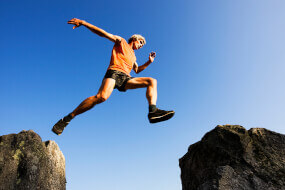 Man taking a big leap, jumping from a big rock to another