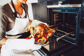 Woman takes a roasted chicken out of the oven
