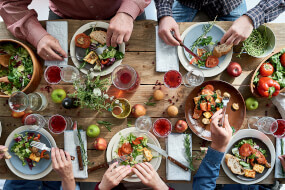 Aerial view of people eating healthy food on a wooden table