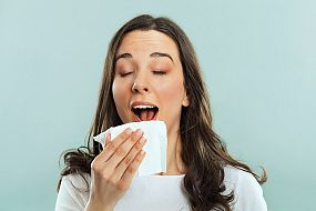 Woman sneezing in a tissue