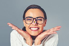 Woman with glasses and a flower on her nose smiling