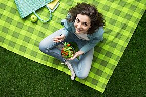 Woman on a picnic blanket eating a salad looking up at the camera