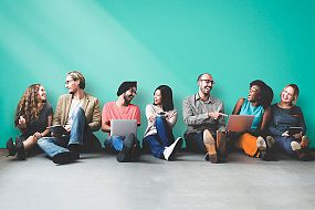 A group of people sitting on the floor against a turquoise wall with their laptops, talking and laughing