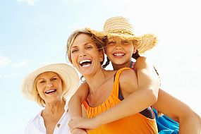 Three generations -  daughter, mother and grandmother, smiling at the beach, wearing sun hats