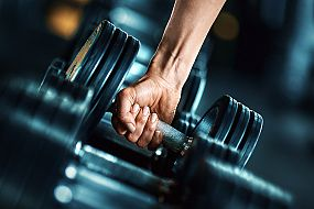Hand picking up a dumbbell