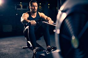 Fit man working out on a rowing machine